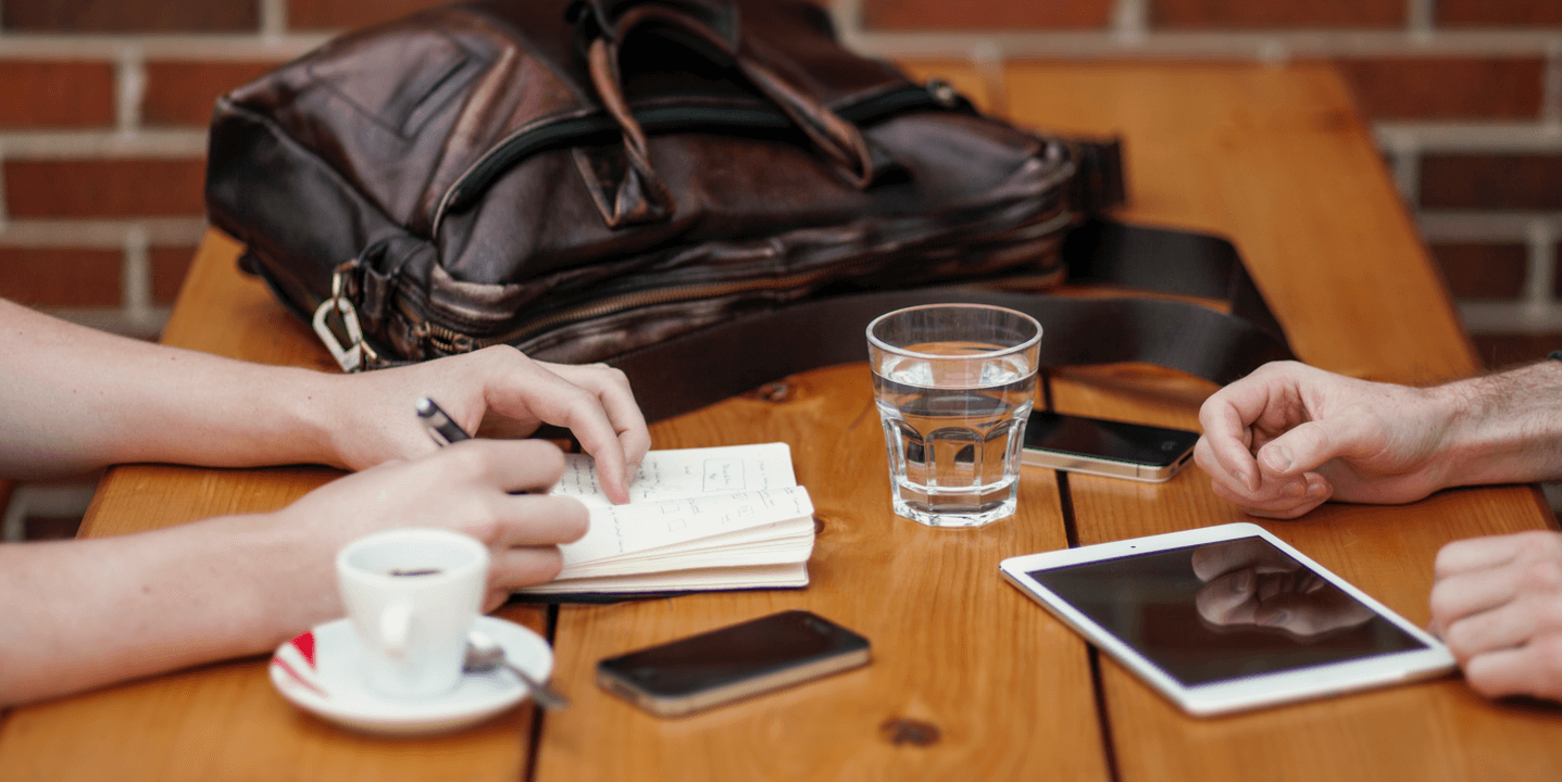 Two people at a table with a tablet, phones, a notepad and coffee