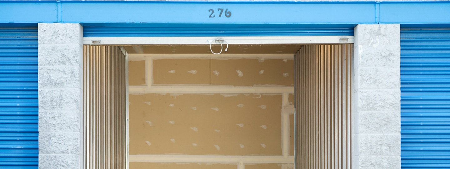 An empty storage unit with a blue door