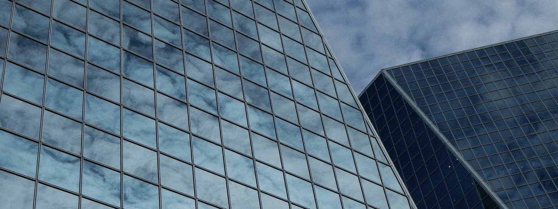 High rise building facades against a cloudy blue sky