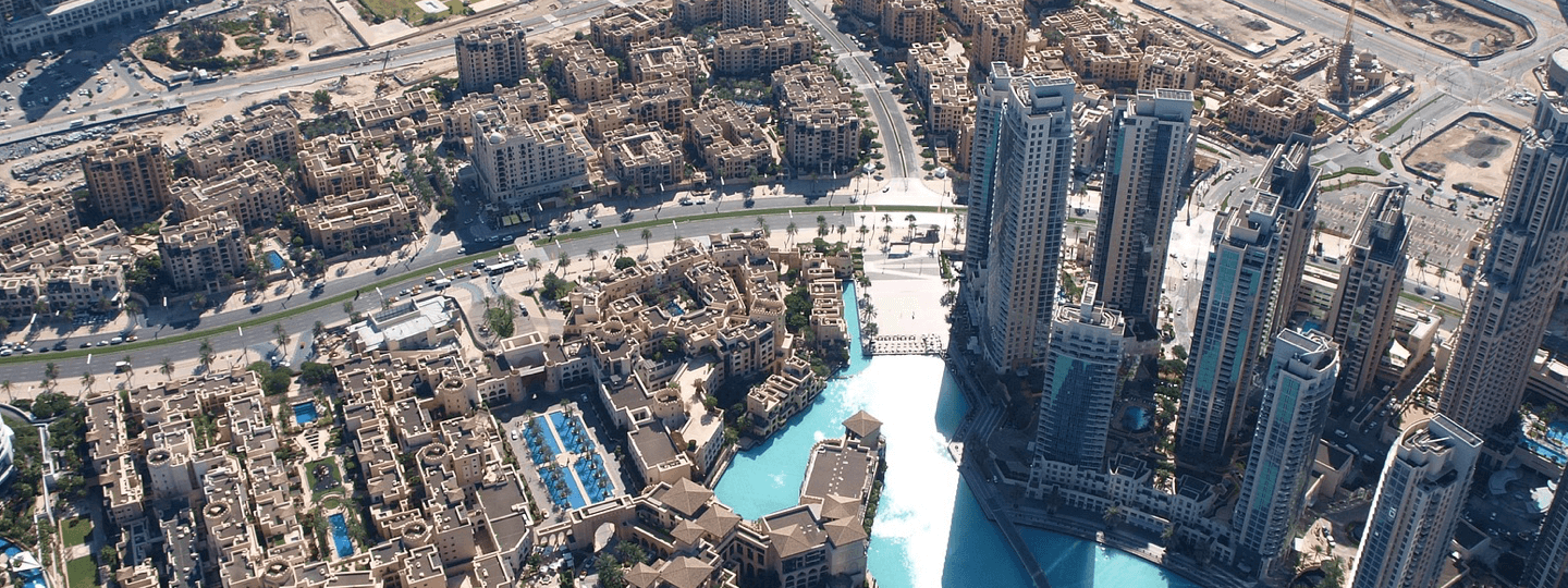 Aerial view of high rise buildings next to smaller buildings and a lake