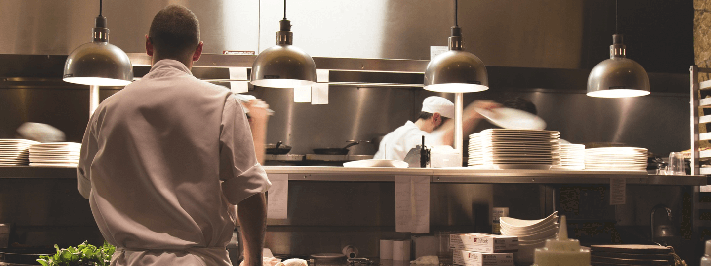 Several cooks working in a resteraunt kitchen