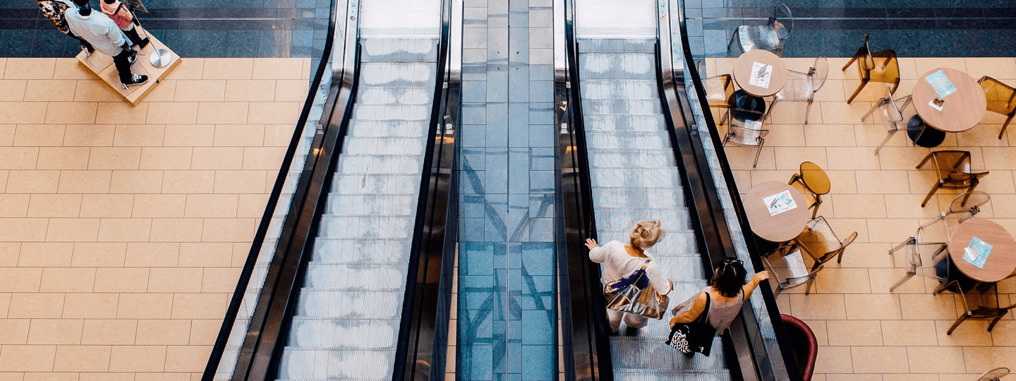 Top down view of Two females riding down an escalator in a mall