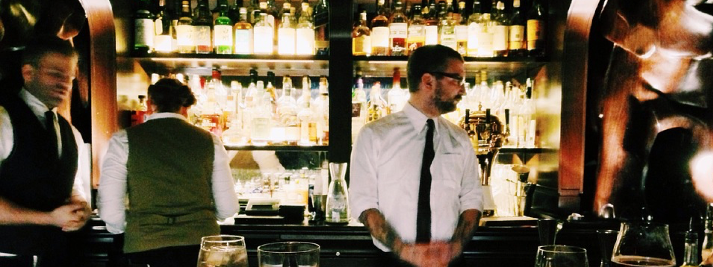 Inside view of an upscale bar with rows of liquor behind a bar tender