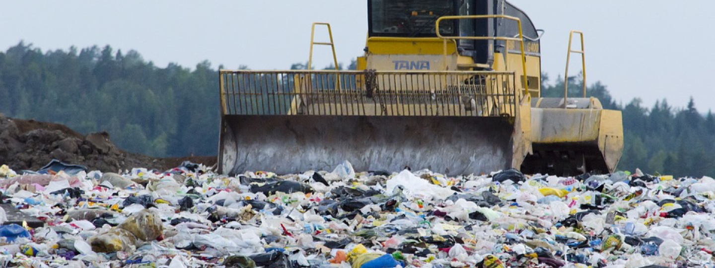 A large compactor working in a landfill