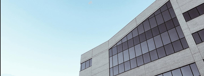 An upper corner of an office building against a blue sky