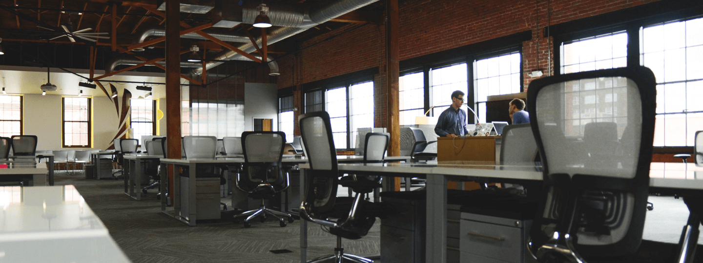 Two males in a large, open, brick office space