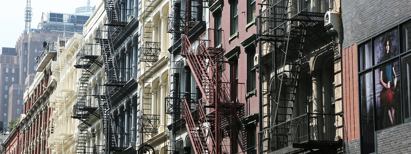 Tall buildings with fire escapes in a large city