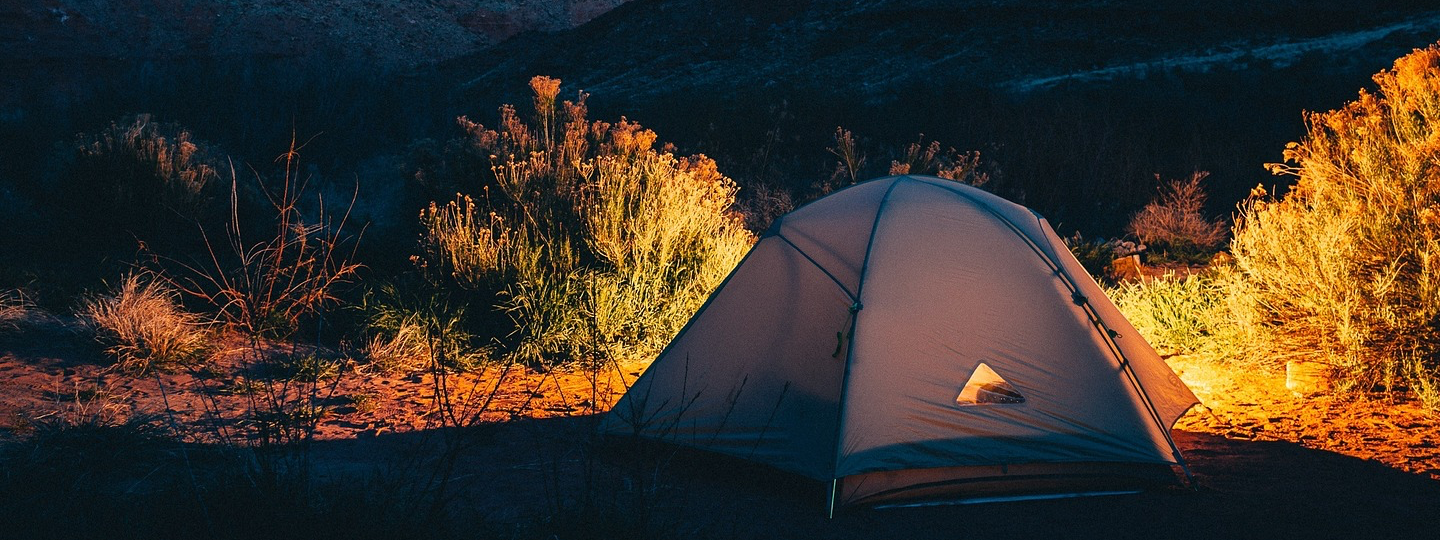 A partially lit up tent amongs sagebrush bushes at dusk
