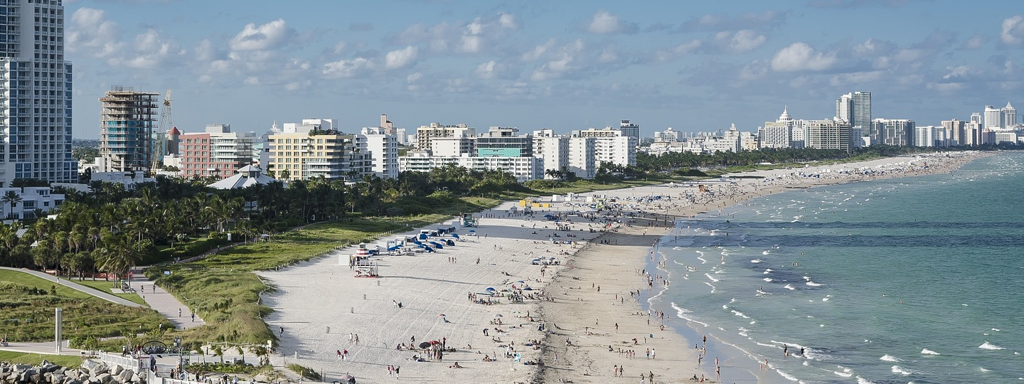 A very large, crowded beach next to a row of highrise buildings