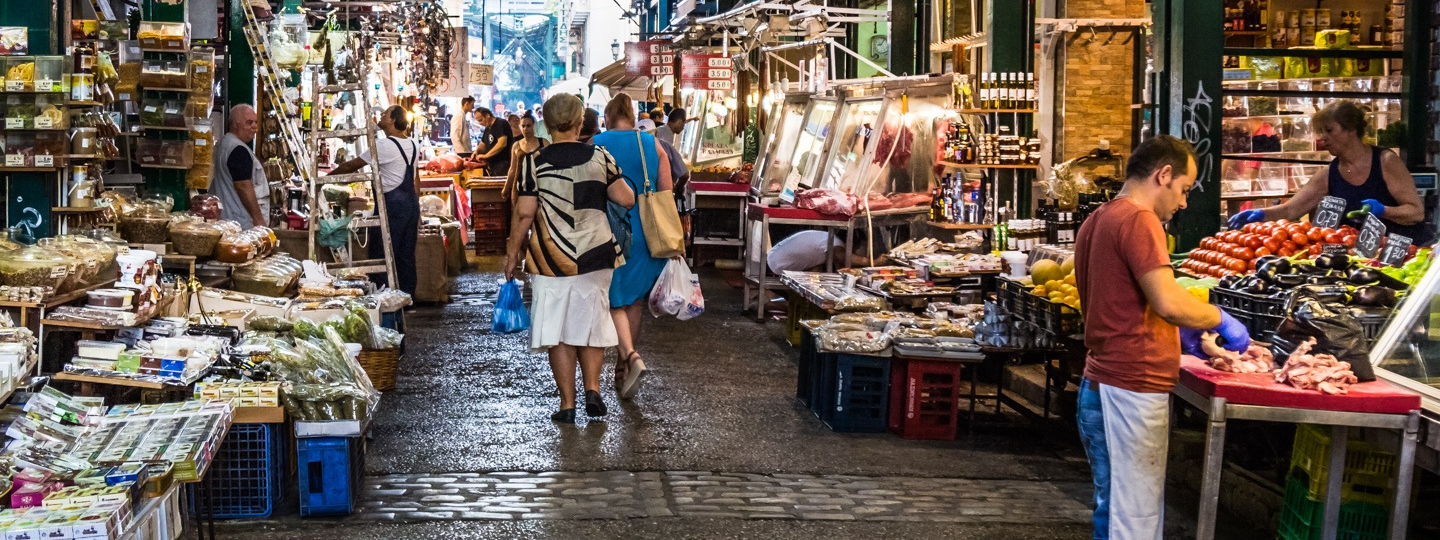 People walking through an open air market with many vendors