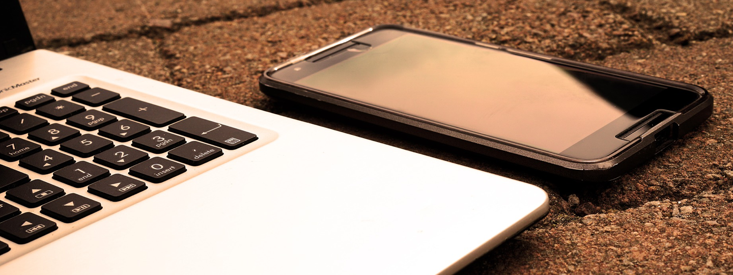 An iPhone sitting next to a laptop