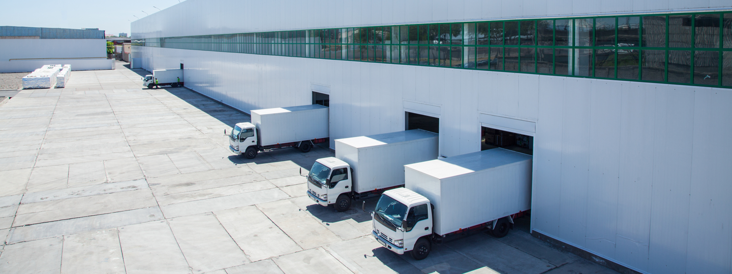 Four trucks in loading docks at a very large warehouse