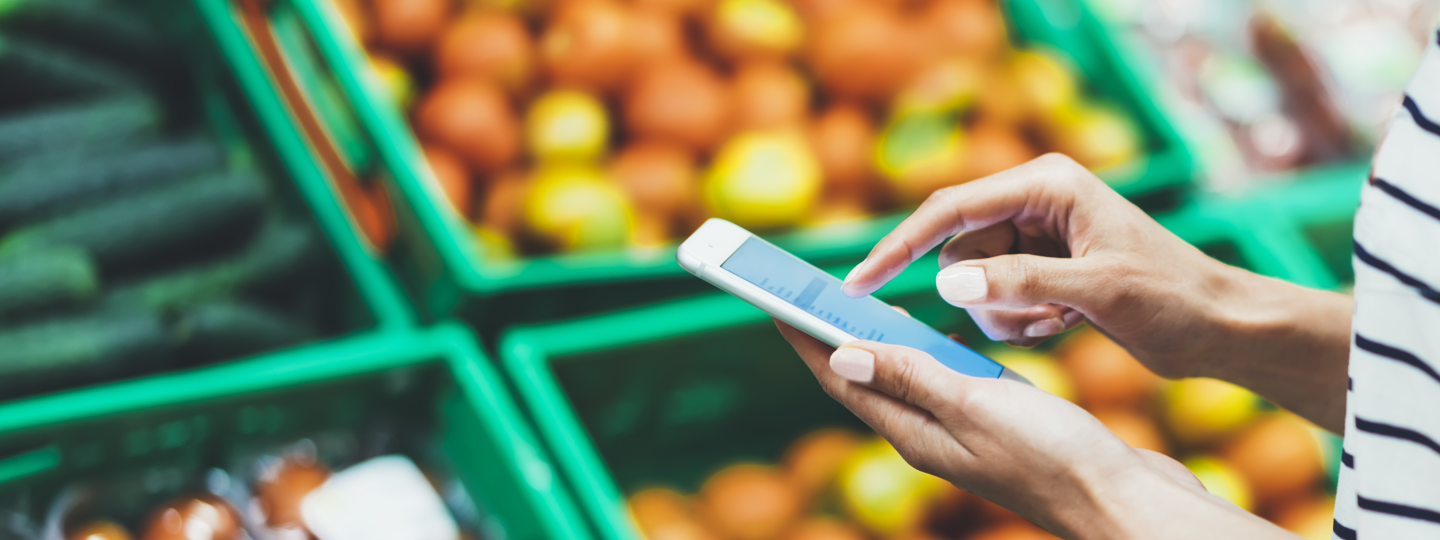 A person on an iPhone in front of baskets of fruit and vegetables